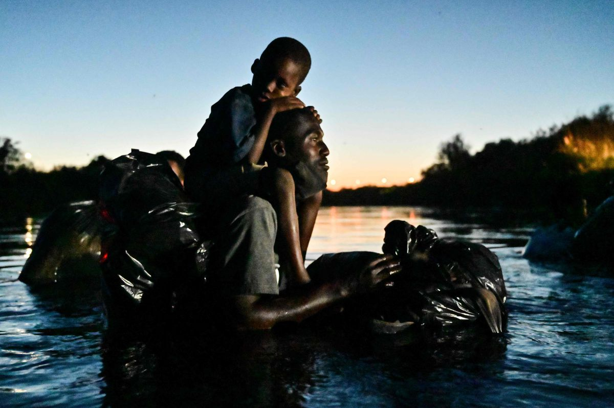 A man carries a child on his shoulders as Haitian migrants cross the Rio Grande river between Ciudad Acuna, Coahuila state, Mexico, and Del Rio, Texas, on Sept. 23, 2021.