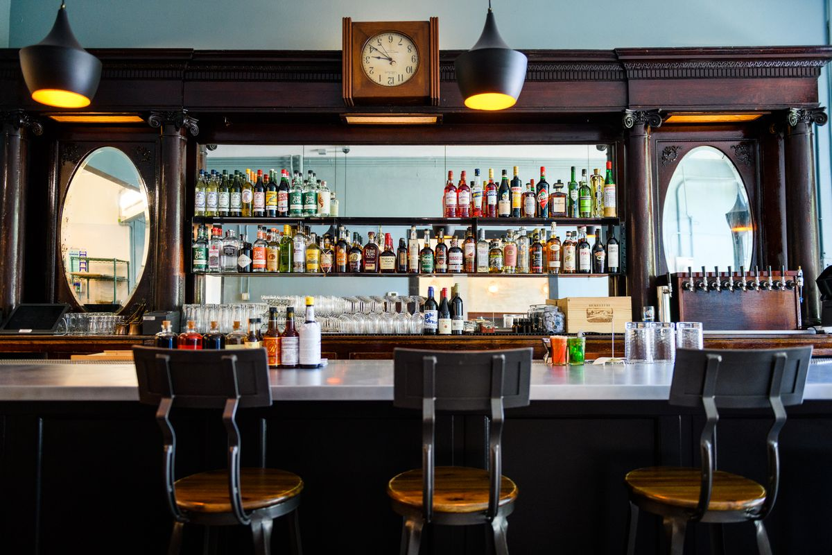 Three barstools with wooden seats and metal backs sit in front of a white bar counter at Yalla, with a view of bottles behind.