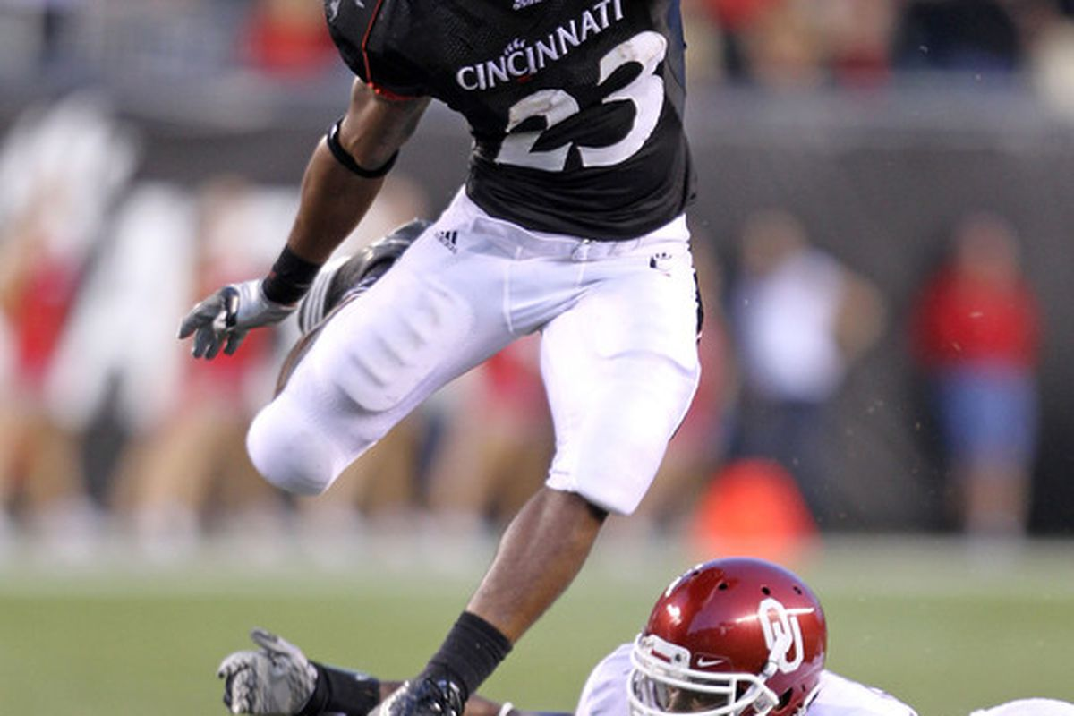CINCINNATI - SEPTEMBER 25: Isaiah Pead #23 of the Cincinnati Bearcats runs with the ball while defended by Tony Jefferson #1 of the Oklahoma Sooners at Paul Brown Stadium on September 25 2010 in Cincinnati Ohio.  (Photo by Andy Lyons/Getty Images)