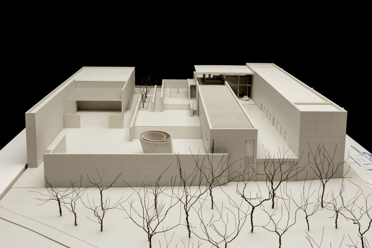 A structural, geometric white one-story model with long rectangular structures and leafless trees in the front courtyard.