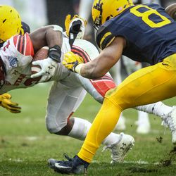 Utah Utes running back Zack Moss (2) is wrapped up by West Virginia Mountaineers defensive lineman Ezekiel Rose (91) and safety Kyzir White (8) at the Zaxby's Heart of Dallas Bowl between the Utah Utes and the West Virginia Mountaineers in Dallas Texas on Tuesday, Dec. 26, 2017.