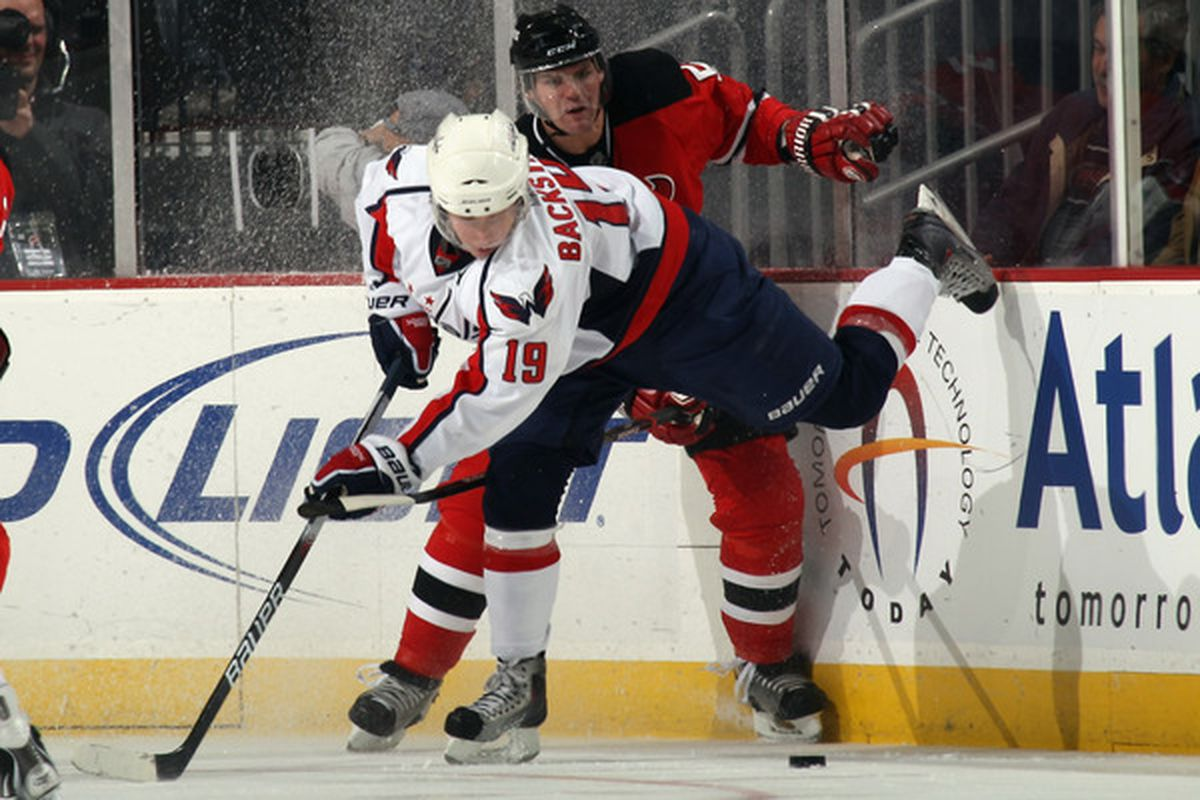 NEWARK NJ - NOVEMBER 22:  Colin White #5 of the New Jersey Devils checks Nicklas Backstrom #19 of the Washington Capitals at the Prudential Center on November 22 2010 in Newark New Jersey.  (Photo by Bruce Bennett/Getty Images)