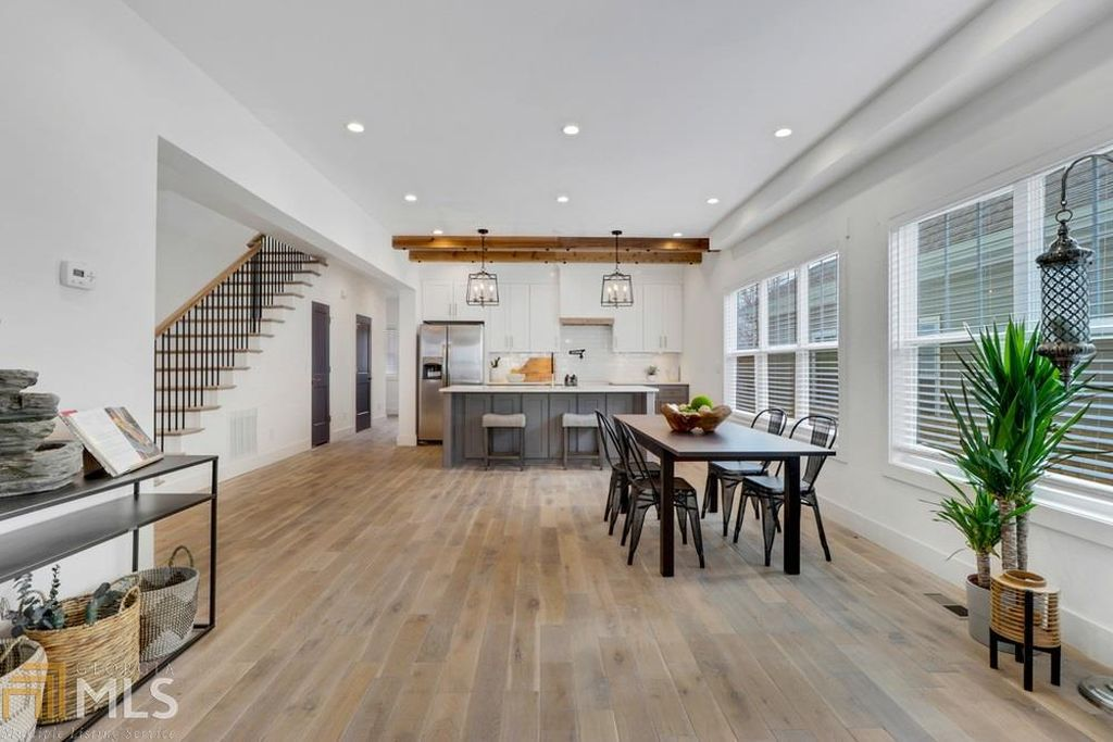 A large white space with kitchen and dining.