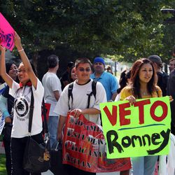 A coalition of activists protests outside the Grand America Hotel as Mitt Romney visits Salt Lake City, Tuesday, Sept. 18, 2012.