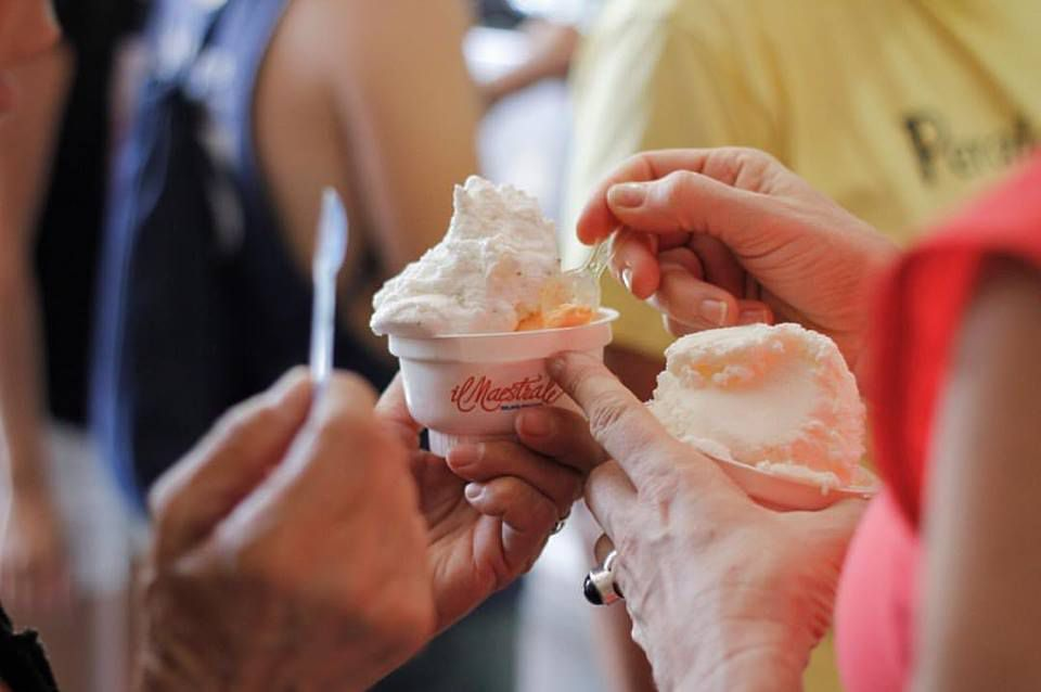 Hand of unseen women hold cups of gelato and take small scoops with little plastic spoons