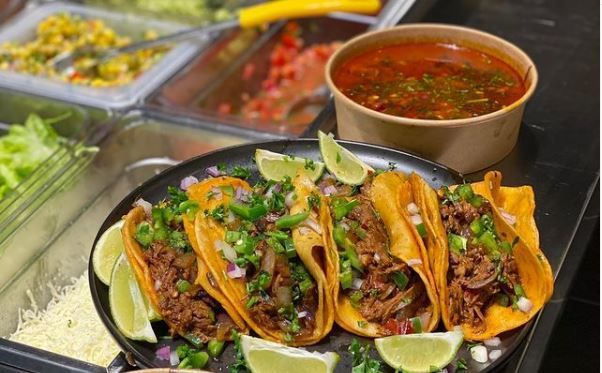A number of reddish tacos filled with red meat, with red soup on the side against a backdrop of a serve yourself steam table.