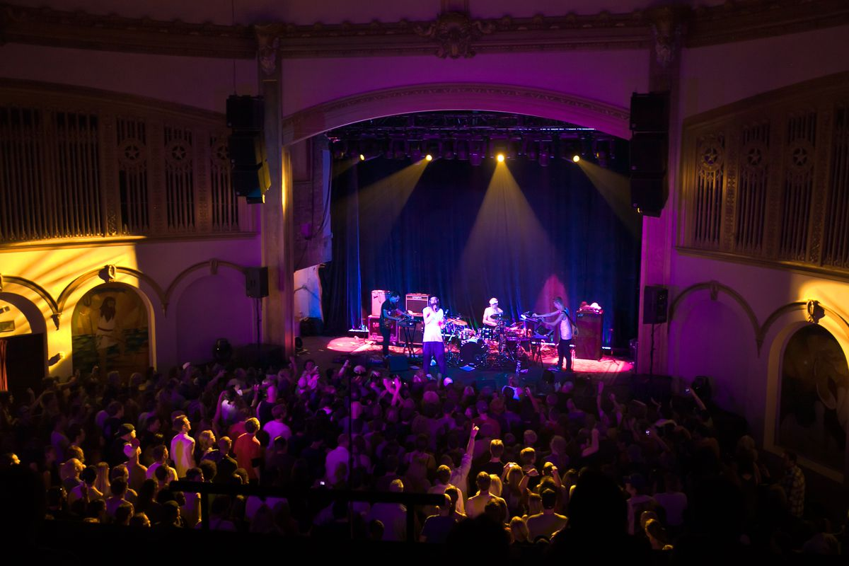 The musician Matisyahu takes the stage with his band at the Neptune Theater, in front of a large crowd bathed in purple and yellow stage lighting.