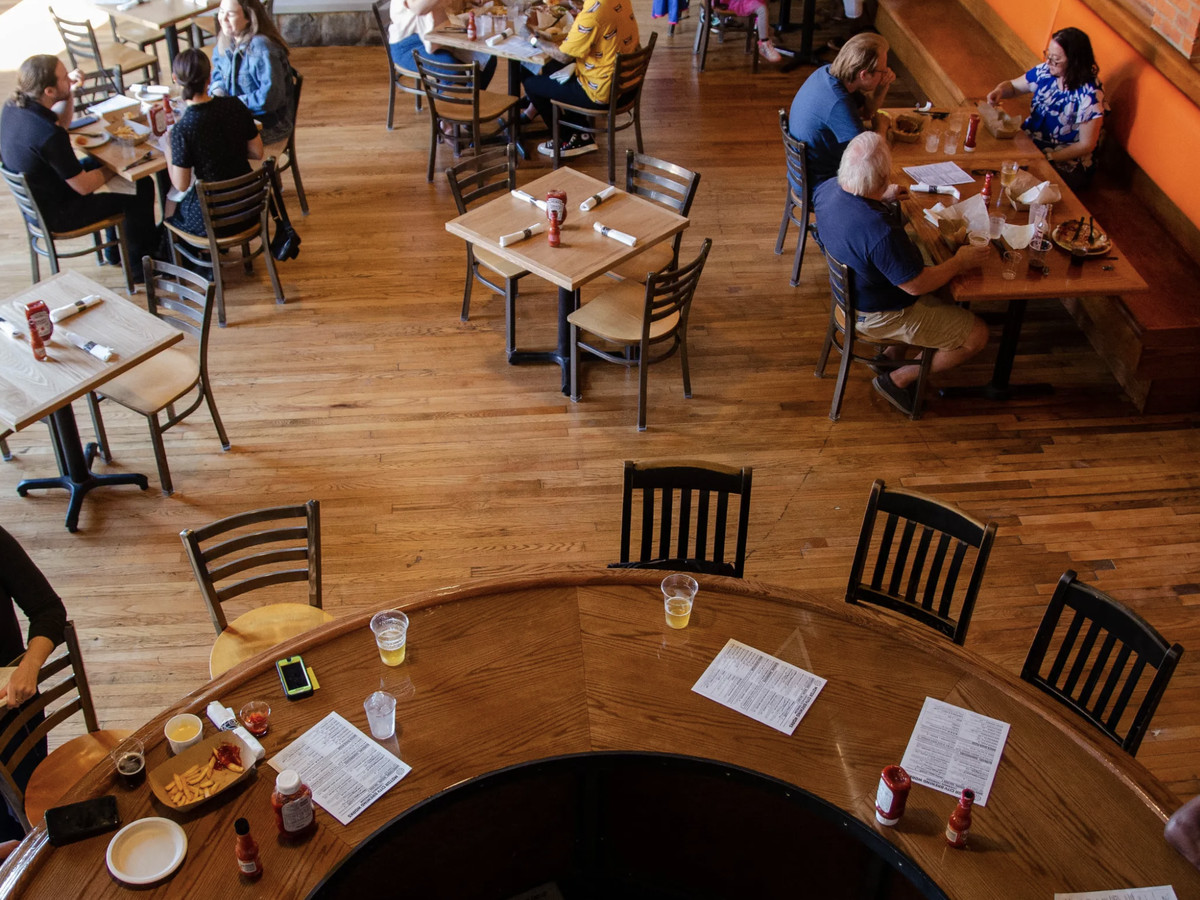 A shot overlooks the main room of the microbrewery from the balcony. The taproom includes a few tables (shown with patrons) and bar seating.