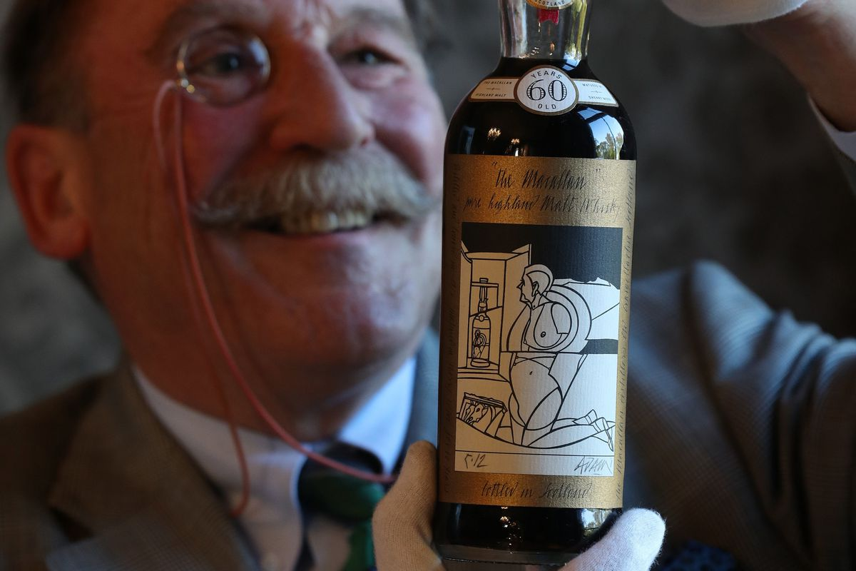A monocled man, Charles MacLean, inspects a bottle of whisky