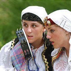 15-year-olds Aisa Tatic, left, and Nina Dzanic, members of the Bosnian folk group Kolo talk during a recent performance at Liberty Park.