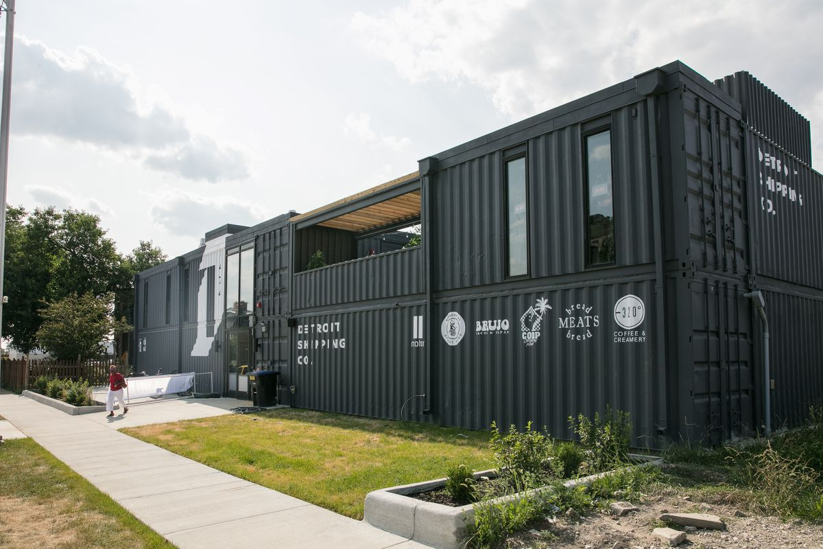 The exterior of Detroit Shipping Company is made up of black modified shipping containers with white stenciled signage.