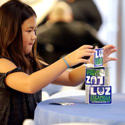 Aria Cook builds a card house out of stickers during a primary election party for Salt Lake City mayoral candidate Luz Escamilla at the Utah State Fairpark in Salt Lake City on Tuesday, Aug. 13, 2019.