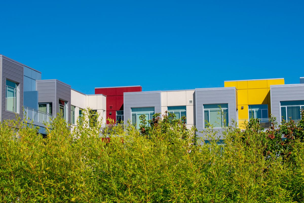 A set of buildings, in red, yellow, and white, shrouded by trees.
