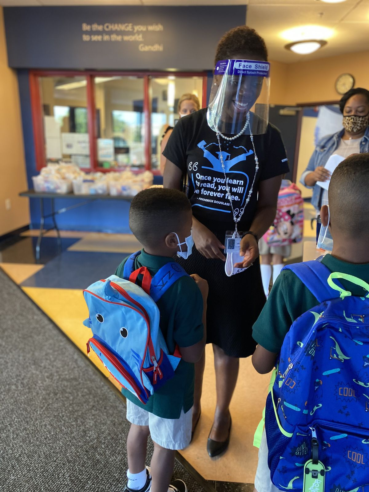 Jennifer Brown, the executive director of KIPP Jacksonville, wears a face shield while talking with students on the first day of school.
