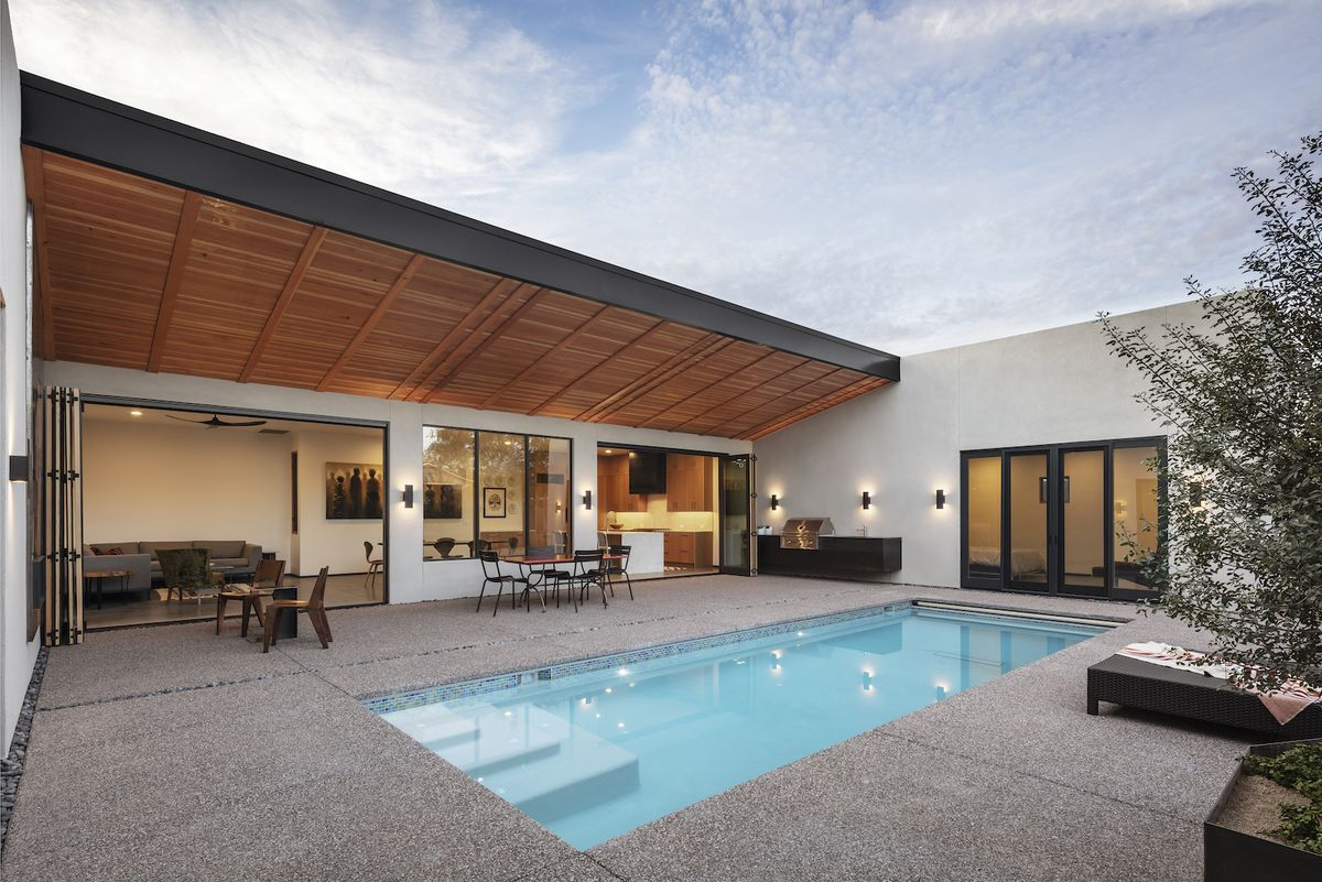 In the foreground is a swimming pool. The pool is adjacent to a house. There is a lounge area near the pool with tables, chairs, and a barbecue.