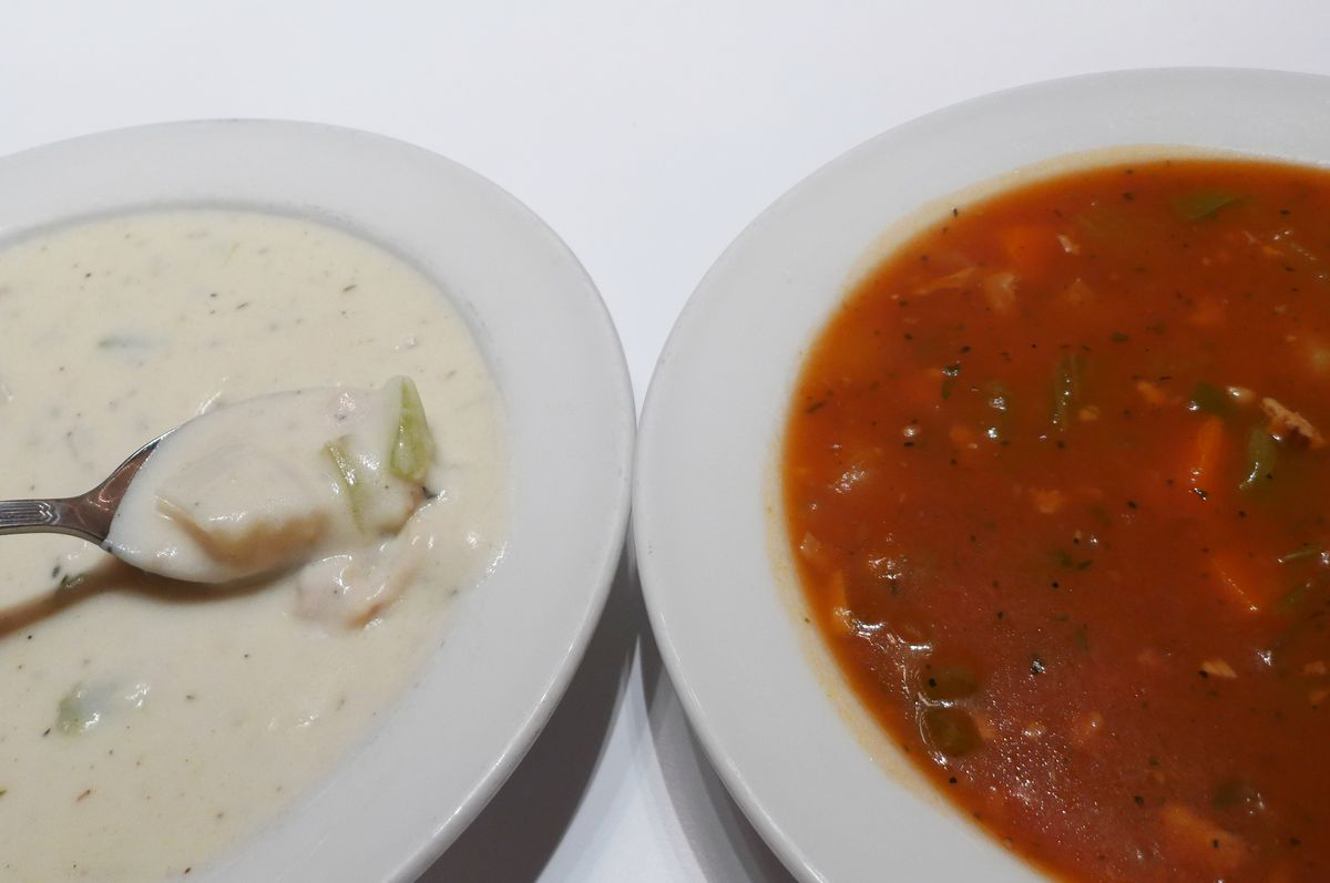 Two bowls of chowder, one white, one red, with a spoon lifting up a bite of the white...