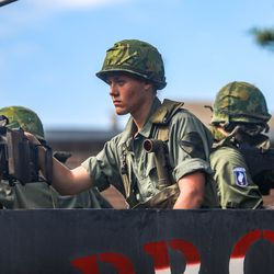 People ride on a military vehicle during the Grand Parade in Provo on Monday, July 5, 2021.