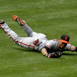 San Francisco Giants' Gregor Blanco makes a diving catch on a line drive hit by Arizona Diamondbacks' Ryan Roberts during the fourth inning in an MLB baseball game Sunday, April 8, 2012, in Phoenix.