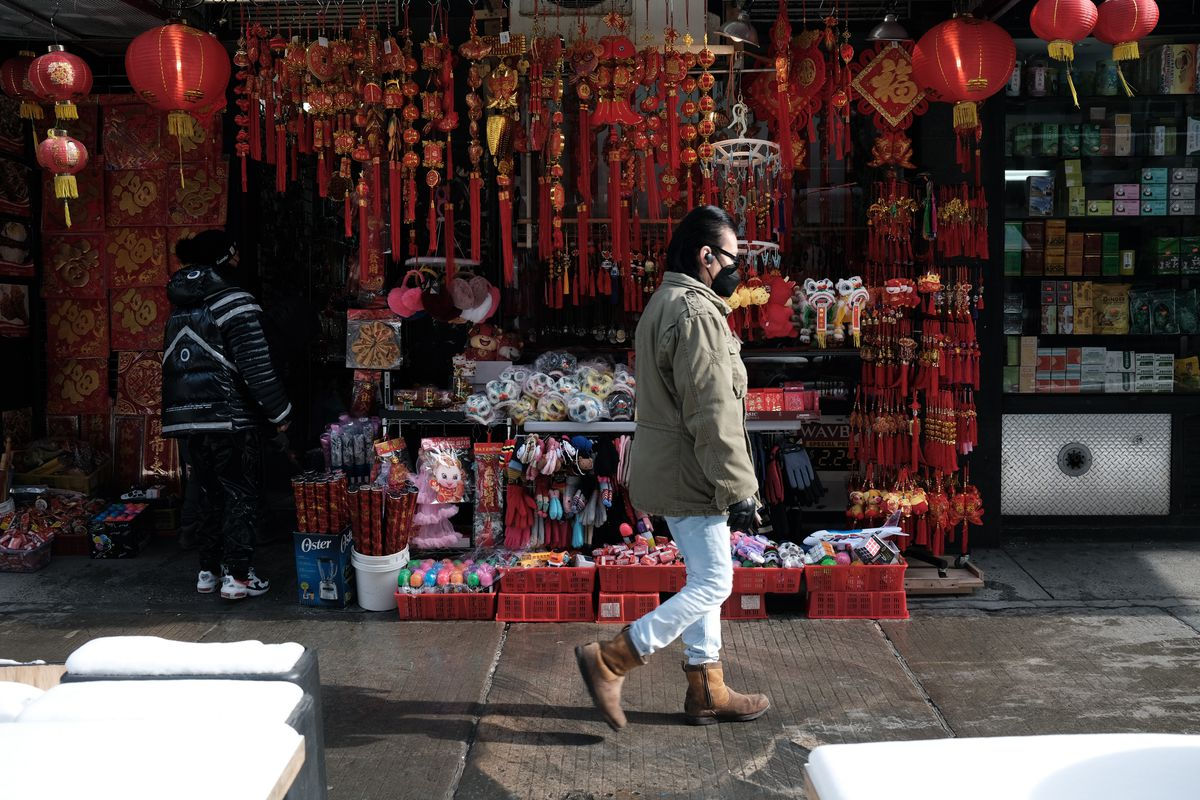 Man wearing mask walks by Chinatown shop with Lunar New Year decorations displayed.