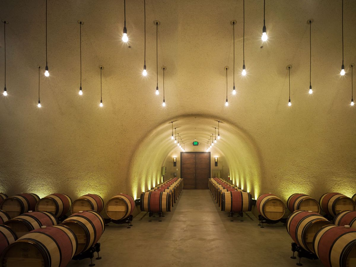 The interior of Ovid Vineyard in California. There are multiple barrels. There are lights hanging from the ceiling. The ceiling is arched.
