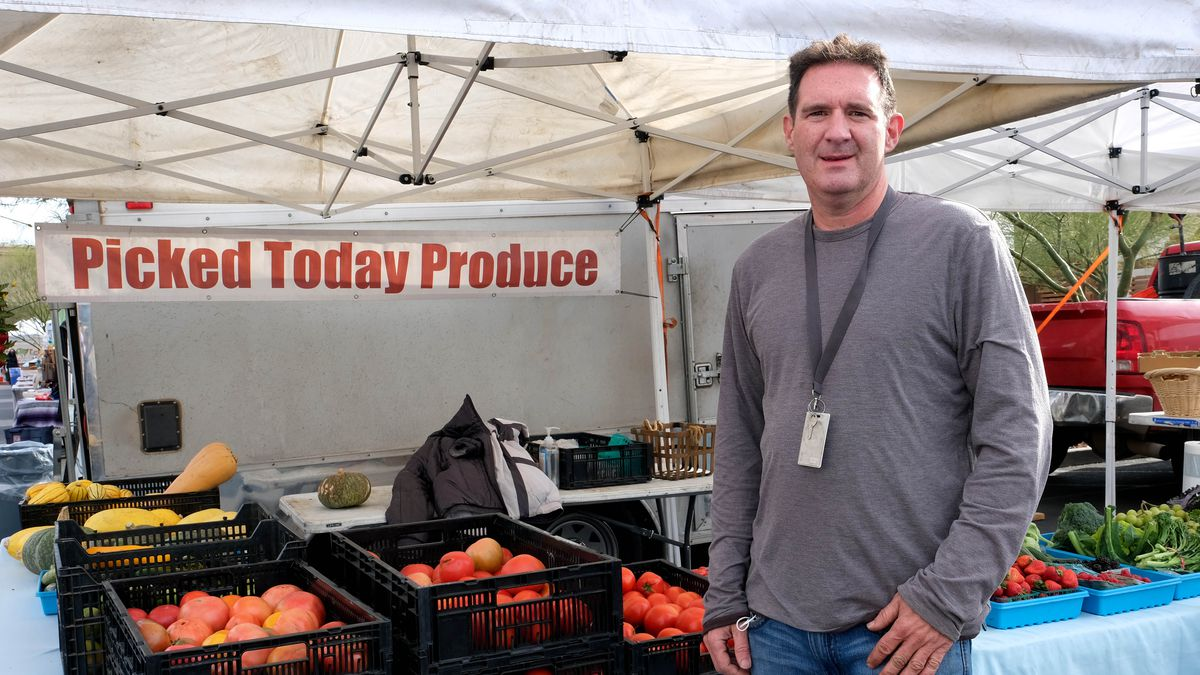 A man stands in front of a produce stand