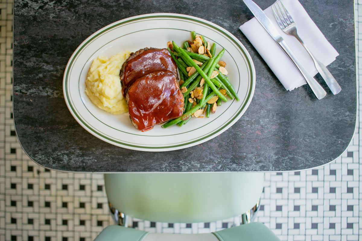 White mashed potatoes, brown meatloaf, and green string beans arranged on a white oval plate sitting on a grey tabletop with a napkin, fork, and knife off to the side