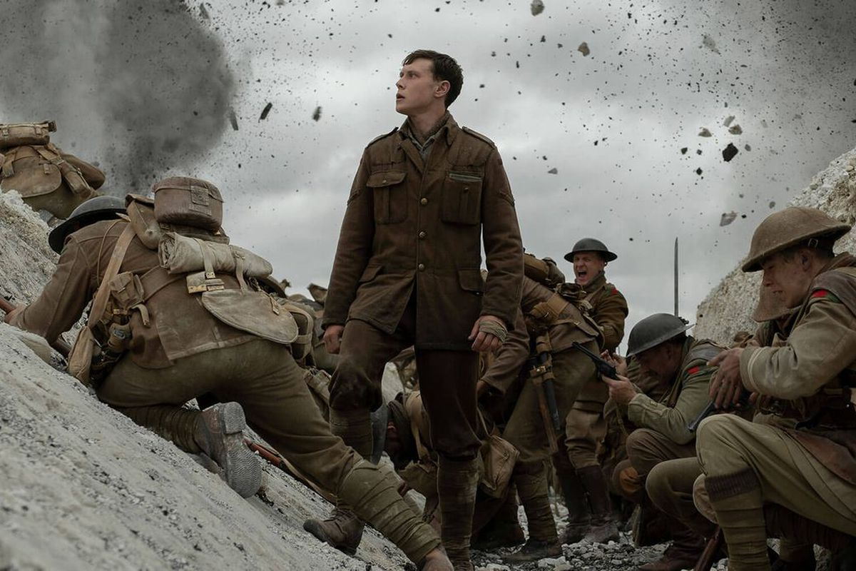 A young soldier played by George MacKay stands in the trenches as bullets fly overhead.