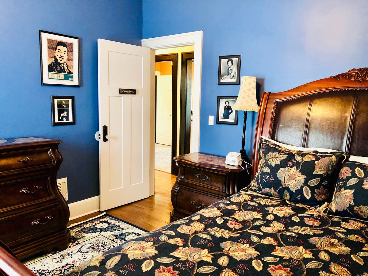 A bedroom with a blue-painted wall and several framed photos of Smokey Robinson. There's a wood dresser and side-table next to the bed.