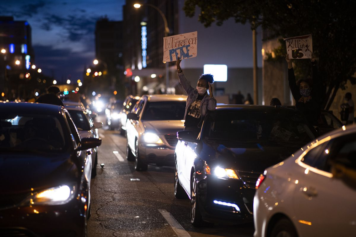 """A line of cars in the dark. Two women lean out of one car, one holding a sign reading """"Where's our peace."""""""