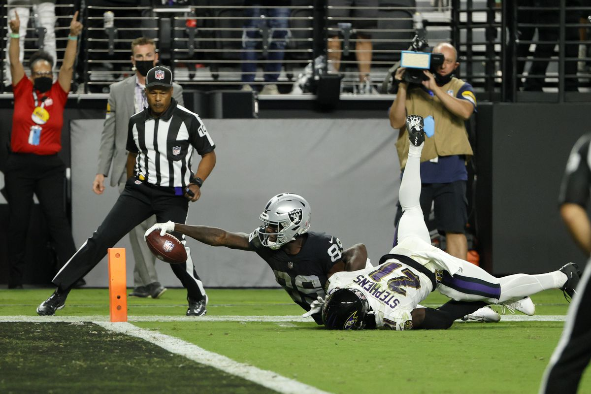 Bryan Edwards #89 of the Las Vegas Raiders reaches for the end zone against Brandon Stephens #21 of the Baltimore Ravens after a 32-yard pass play that was initially ruled a touchdown but was called down at the 1-yard line after a review during overtime at Allegiant Stadium on September 13, 2021 in Las Vegas, Nevada.
