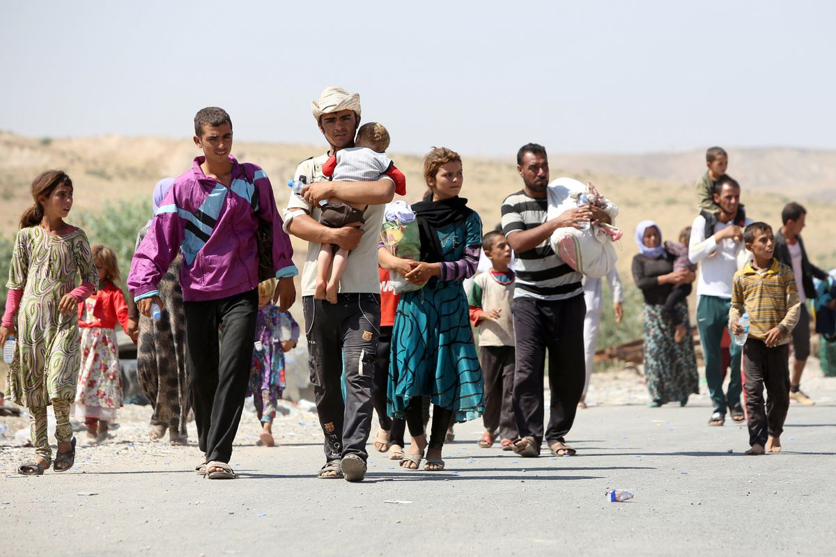 Displaced Iraqis from the Yazidi community carry their children as they cross the Iraqi-Syrian border