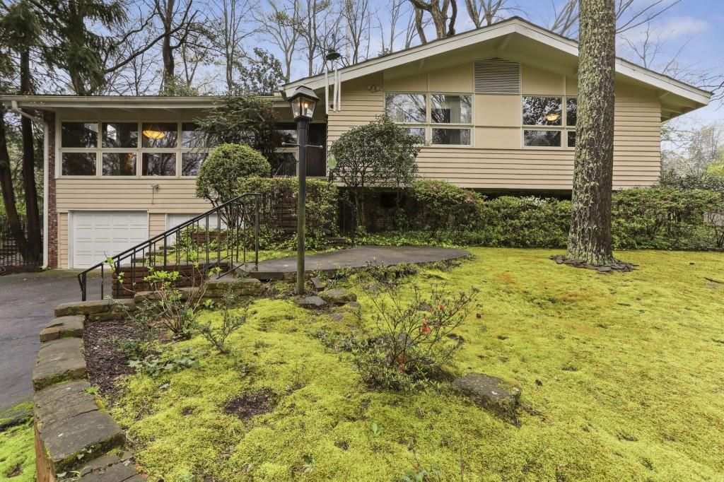 A midcentury home on a little green hill under a lot of trees.