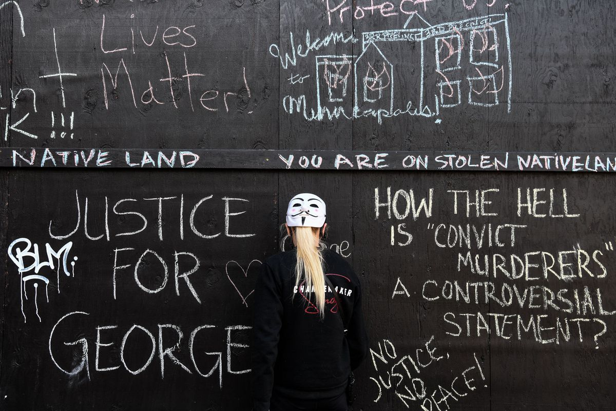 A demonstrator stands in front of a wall with chalk messages demanding justice for George Floyd.