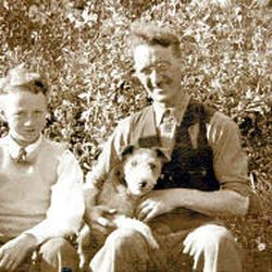 Leslie Norris' father, George Norris, is seen with Leslie's younger brother Gordon and their dog. George worked as an engineer in the mines until a falling rock broke his back.