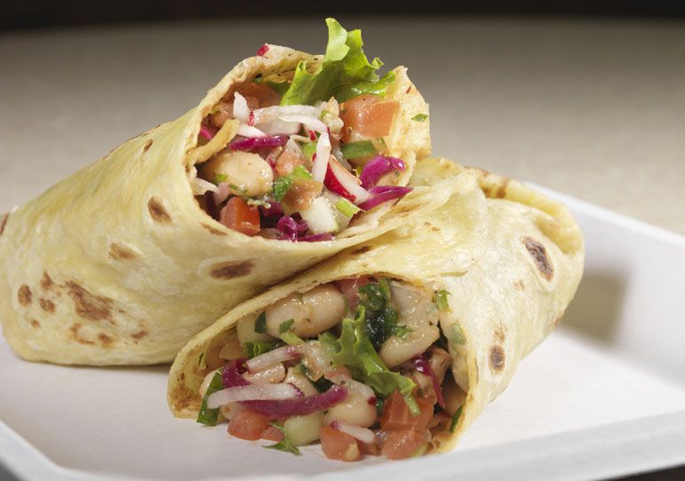 A Mediterranean wrap stuffed with lettuce, red onions, tomatoes, and other ingredients sits on a white plate on a neutral background
