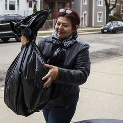 Mirna Torres, 43, receives three days of free breakfast and lunch meals for each of her two kids at William P. Nixon Elementary School, 2121 N. Keeler Ave., Thursday morning, March 19, 2020.