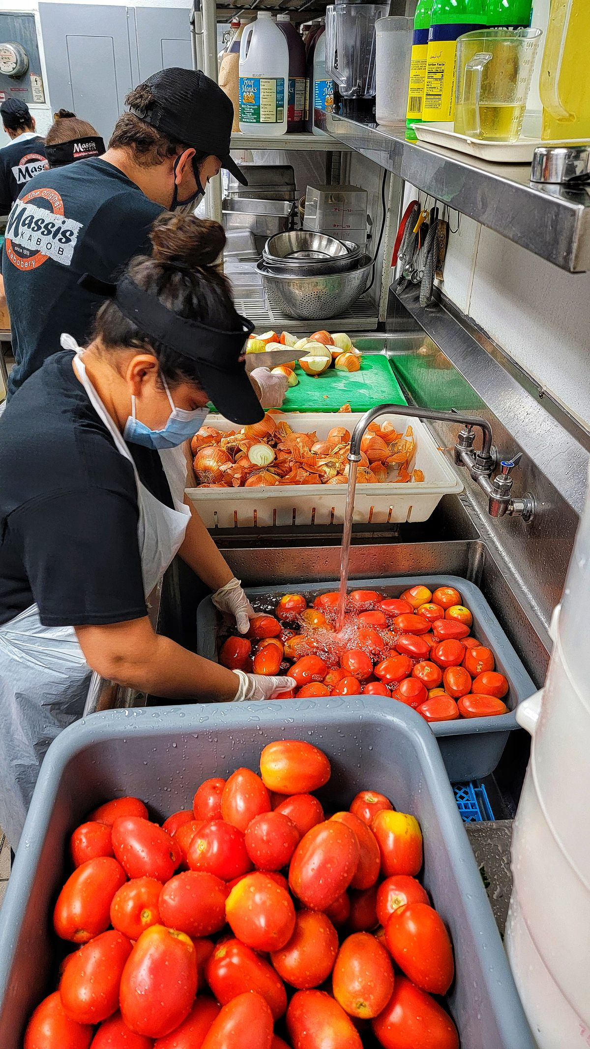 Workers in masks rinse and begin to peel tomatoes inside of an industrial kitchen area.