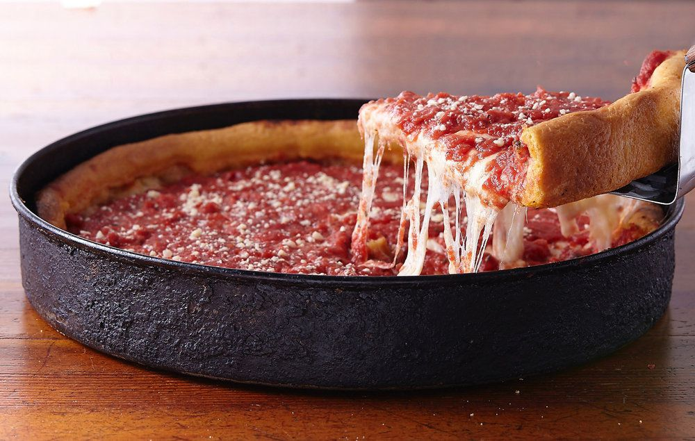A slice of deep dish pizza being lifted out of the pan.