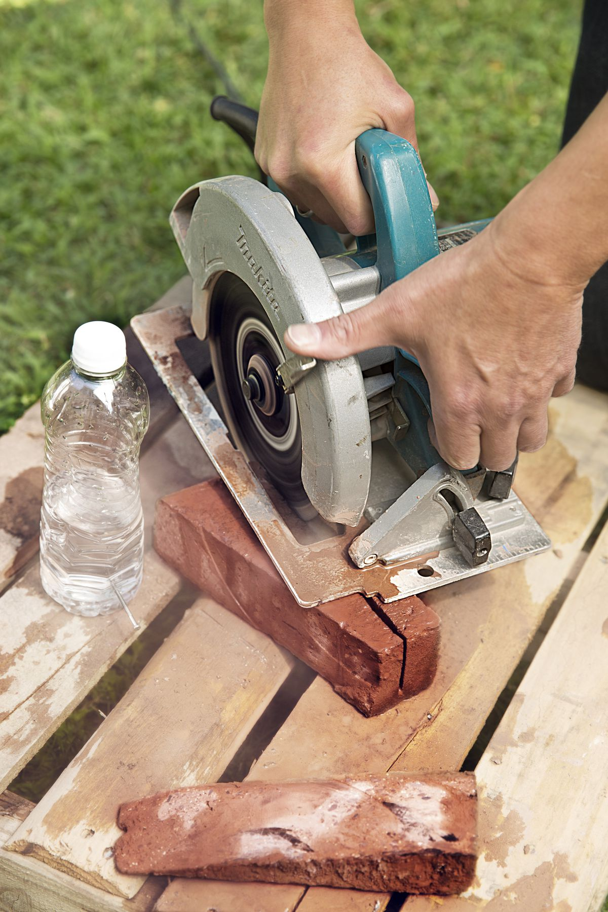 Man Uses Circular Saw To Cut Through Marked Bricks For Brick Garden Edging