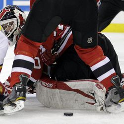 New Jersey Devils goalie Martin Brodeur, bottom, looks at the puck as teammate Andy Greene helps to defend against the Florida Panthers during the first period of Game 4 of a first-round NHL hockey Stanley Cup playoff series on Thursday, April 19, 2012, in Newark, N.J.