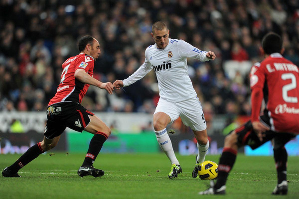 Karim Benzema (R) of Real Madrid scores his sides opening goal past Ivan Ramis of Mallorca during the la liga match between Real Madrid and Mallorca at Estadio Santiago Bernabeu.