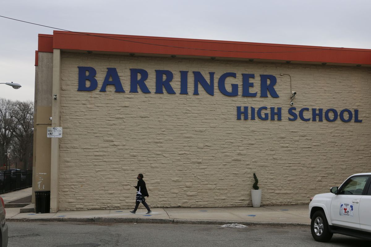 A person walks past the outside of Barringer High School on March 15, 2021.