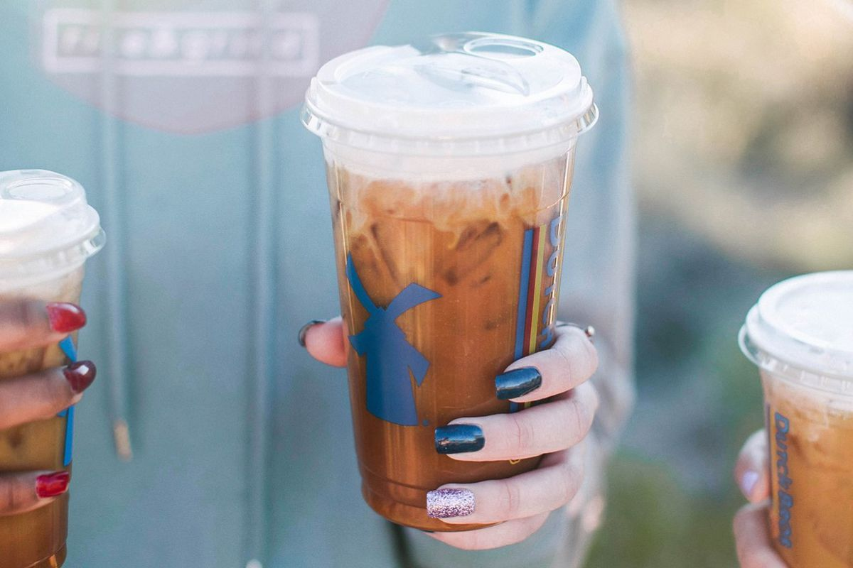 A white woman's hand holds a plastic cup of iced coffee with white foam on top.
