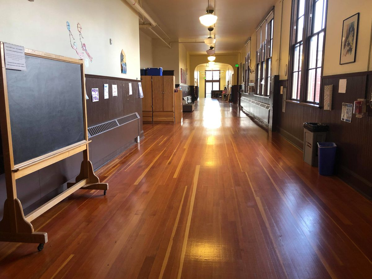 A wide hallway with hardwood floors. A chalkboard on wheels is along the left wall. Both walls are beige with dark brown wainscoting. On the far end of the hall there's a large archway leading to additional space.