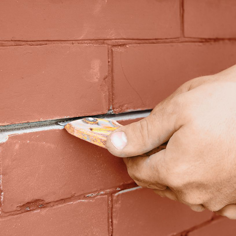 Person scraping between brick joints.