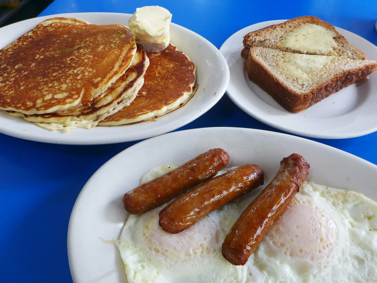 Stack of pancakes, two fried eggs, three sausages, and buttered toast on a bright blue counter.