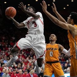 Arizona's Dylan Smith lays an up-and-under basket in past UTEP defenders during the Arizona-University of Texas El Paso game in McKale Center on November 14 in Tucson, Ariz.