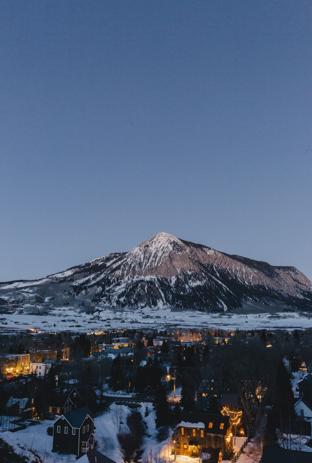 A nighttime view of the town of Crested Butte with lights on in many houses, and a mountain in the background.