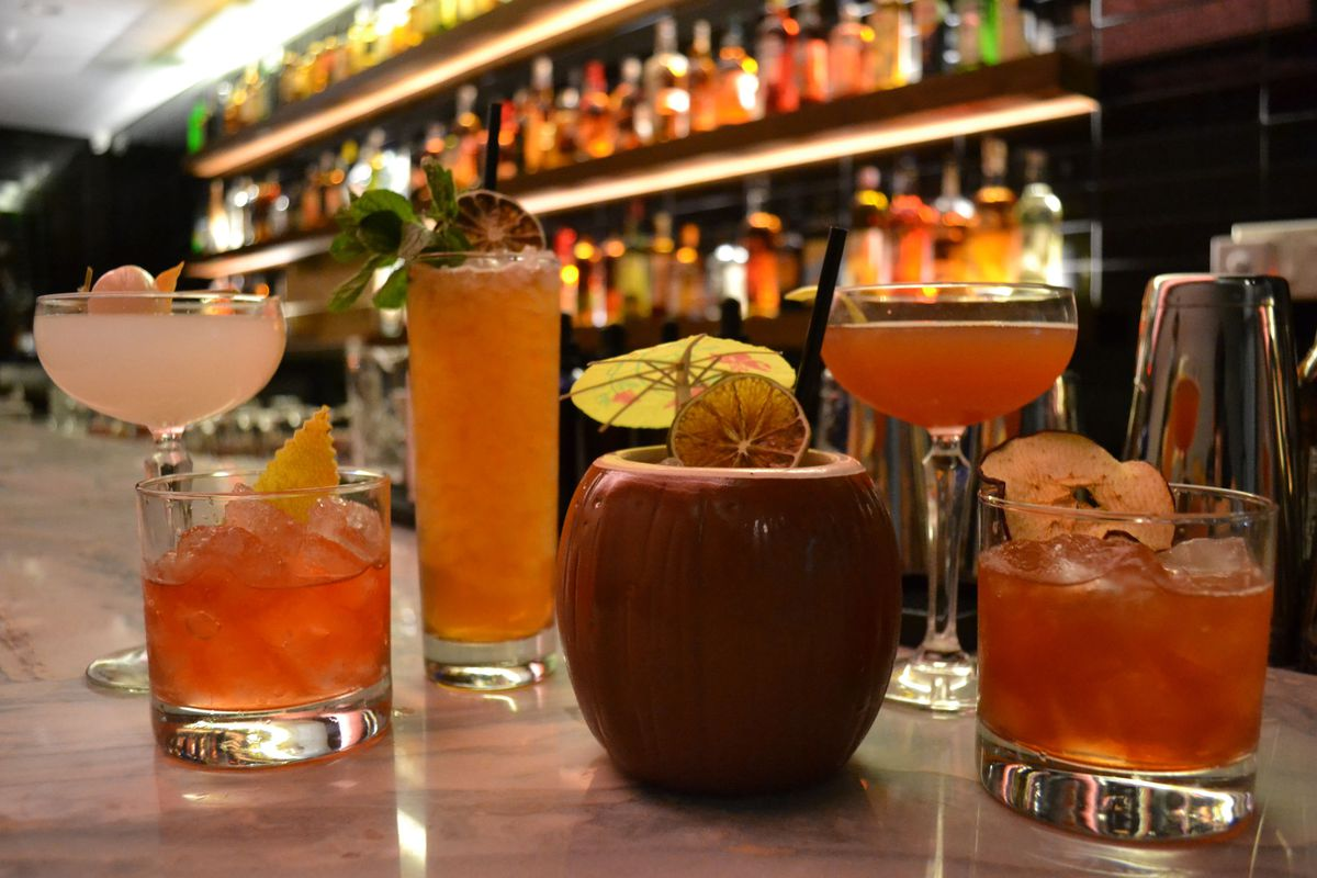 an array of tropical cocktails sintting on a bar, including a drink served in a coconut-shaped mug with a tiny umbrella