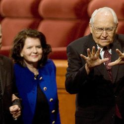 """Elder L. Tom Perry does motions to the Primary song """"Popcorn Popping"""" as he, Elder Russell M. Nelson and Wendy Watson Nelson leave the Conference Center after the Saturday morning session of the 179th Semiannual General Conference of The Church of Jesus Christ of Latter-day Saints on Oct. 3, 2009."""